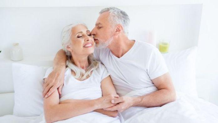 Hombre besando en la mejilla a una mujer.