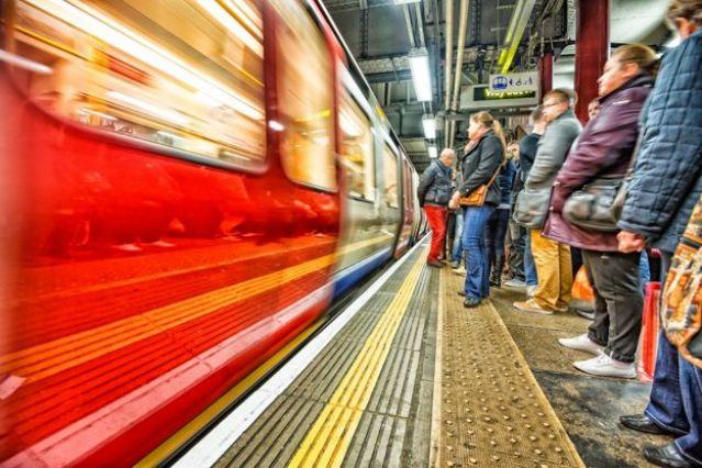 As pessoas esperam o metrô atrás da linha amarela