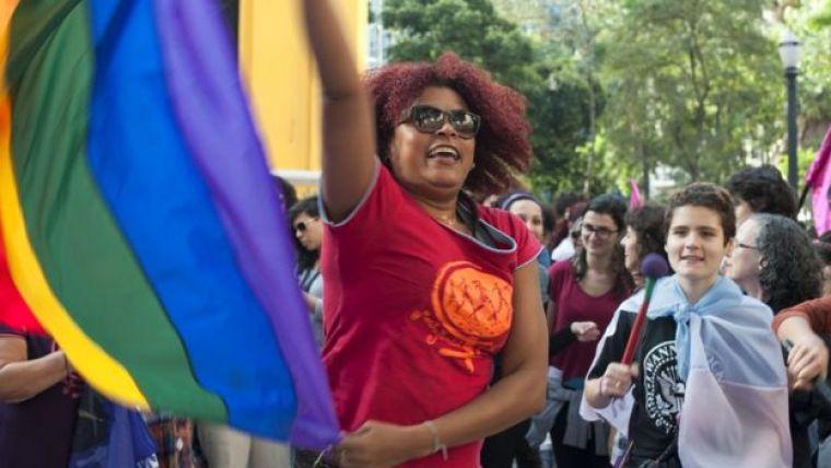 mulher com bandeira do movimento LGBT