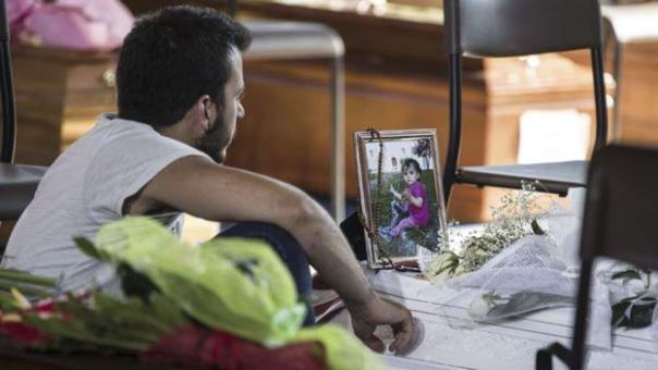 Hombre sentado junto a un féretro que tiene encima un porta retratro con la foto de una niña sobre el que cuelga un rosario