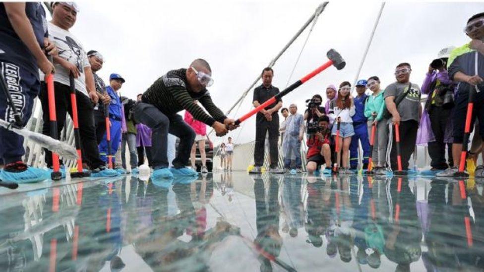 Hombre golpea el cristal del puente de Zhangjiajie con un mazo.