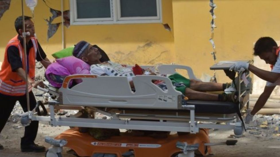 Staff take patients outside as a safety measure at a hospital in Mataram