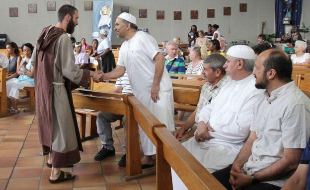 Un monje católico da la bienvenida a fieles musulmanes en la iglesia de Saint-Pierre-de-Lariane, antes de una masa el 31 de julio de 2016, en Niza, Francia del sudeste