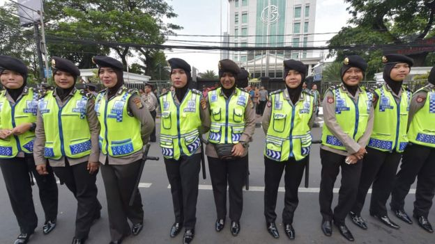 Indonesian policewomen stand guard as Muslims march towards the presidential palace during a protest against Jakarta governor Basuki Tjahaja Purnama also known as Ahok over an alleged blasphemy in Jakarta on November 4, 2016