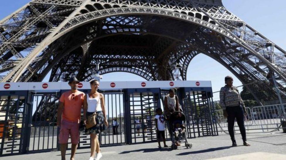 Turistas passeiam ao redor da Torre Eiffel