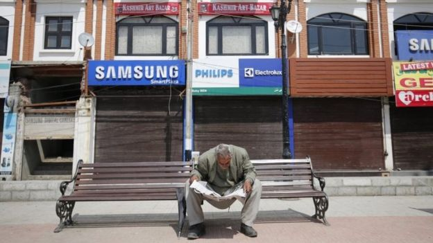 A man reads a newspaper in front of a closed market during a shutdown in Srinagar, the summer capital of Indian Kashmir, 12 April 2016.