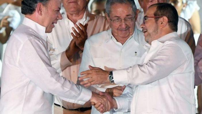 Juan Manuel Santos y y Rodrigo Londoño (comandante de las FARC) se dan la mano en la Habana frente a Raúl Castro.