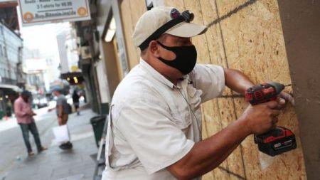 Homem parafusando madeira para proteger imóvel nos EUA