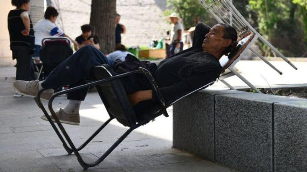 Un Chinois fait la sieste sur une chaise, sur une place publique.