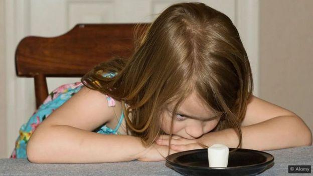 طفلة أمامها طبق به قطعة من الحلوى