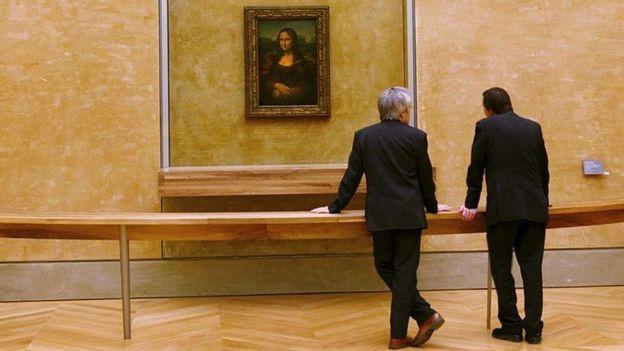 Dos hombres miran la Mona Lisa en el Museo del Louvre en París.