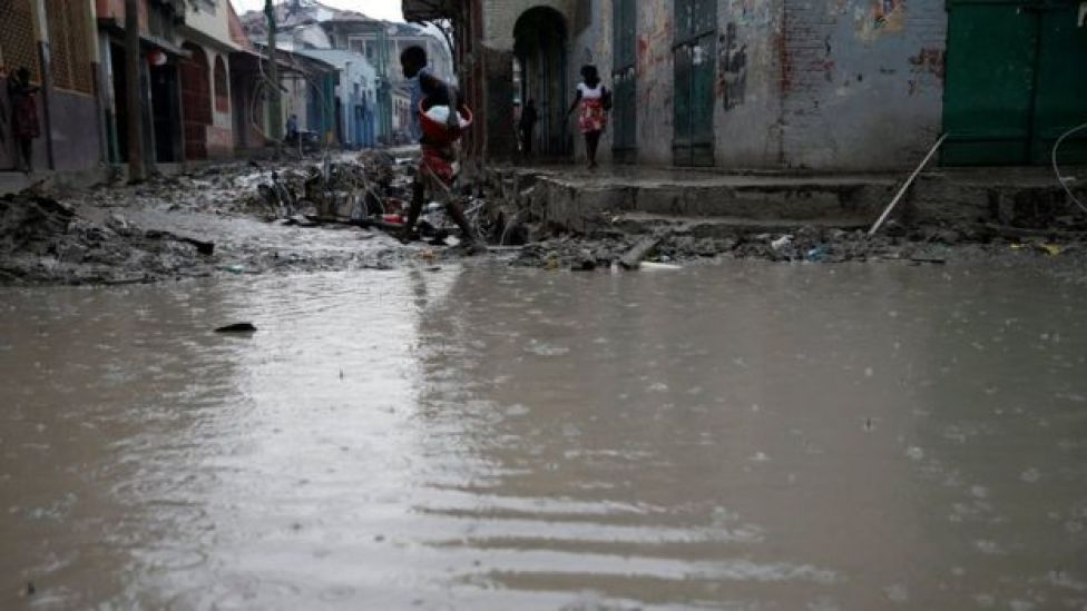 People walk in a flooded street after Hurricane Matthew hit Jeremie