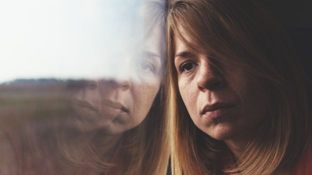 Mulher adulta apoiada no vidro de uma janela, com semblante depressivo