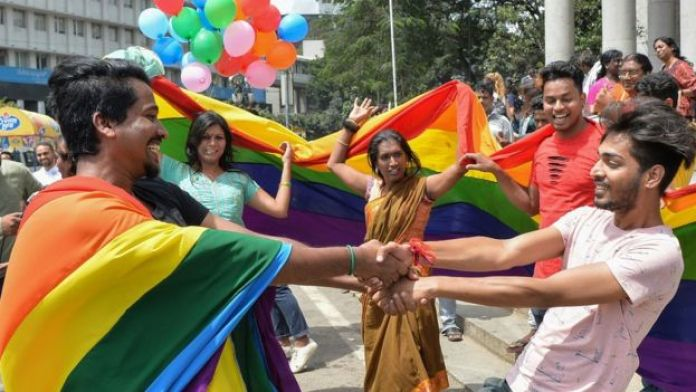 Indian LGBT activists and supporters celebrate the court ruling, dancing and holding up rainbow flags and balloons
