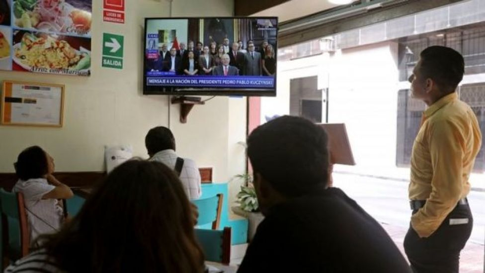 People look on as Peru's President Pedro Pablo Kuczynski addresses the nation as he resigns in Lima, Peru, March 21, 2018.