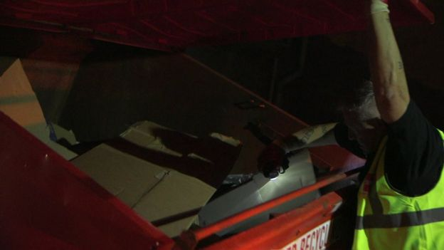 Driver Barry rummages through cardboard in a commercial recycling bin to check for rough sleepers
