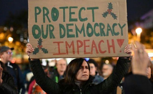 Protestujący trzymają znaki wzywające do impeachmentu prezydenta USA Donalda Trumpa przed budynkiem ratusza w Los Angeles, w Los Angeles w Kalifornii, 17 grudnia 2019 r.