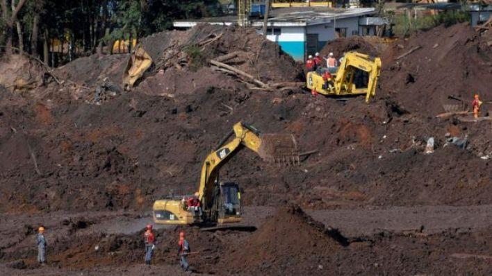 Membros de equipe de resgate buscam as vítimas de colapso de barragem de rejeitos em meio a tratores e muita lama