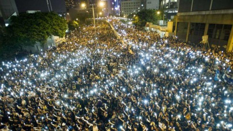 Des manifestants et des étudiants manifestants brandissent leur téléphone portable en signe de solidarité lors d'une manifestation devant le siège du Conseil législatif à Hong Kong le 29 septembre 2014