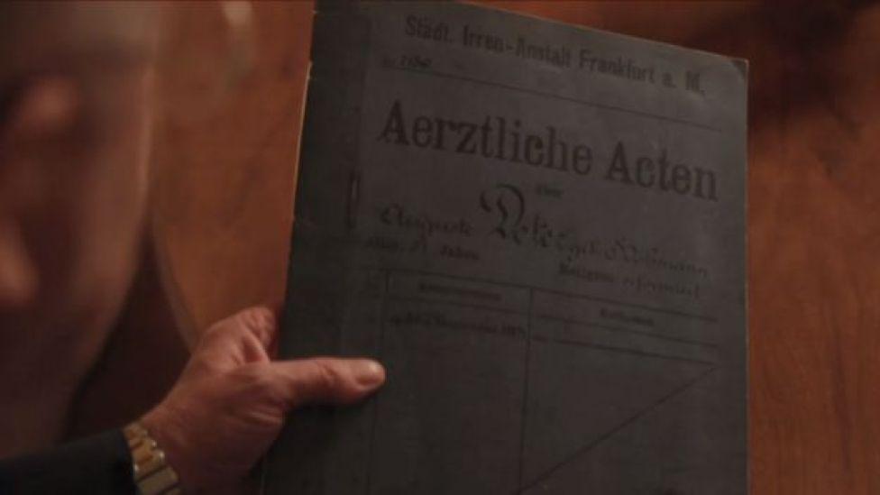 Casi un siglo después, el psiquiatra Maurer lideró una investigación que reexaminó el caso de Auguste. Aquí lo vemos mostrando la carpeta original del doctor Alzheimer.