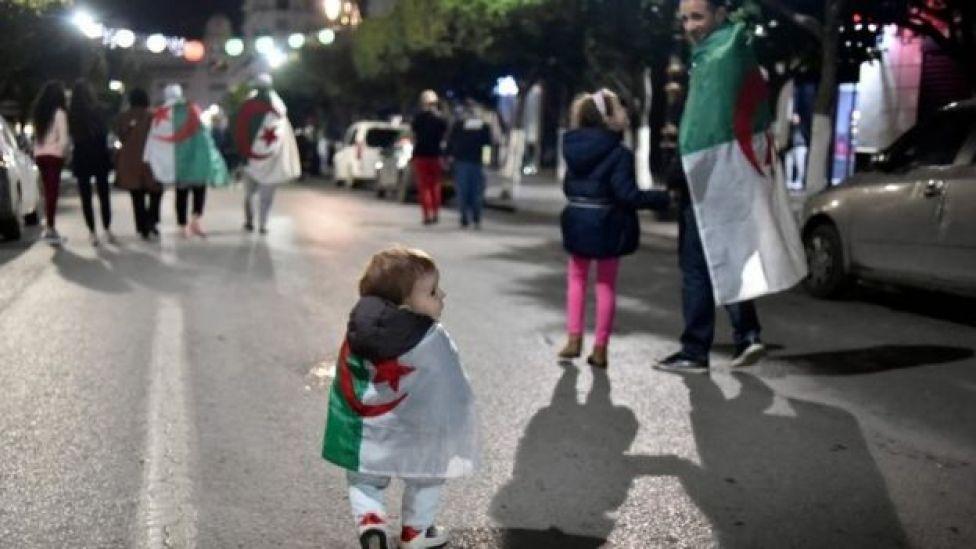 A small child draped in Algeria's national flag celebrates in Algiers. Photo: 2 April 2019