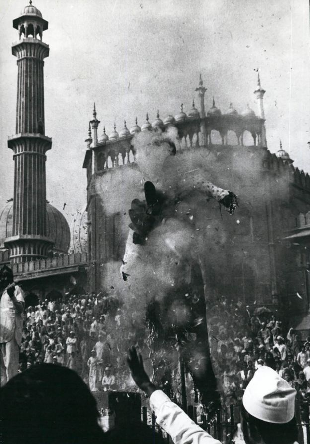 Demonstrators outside the Grand Mosque burn an effigy in protest against the building's seizure