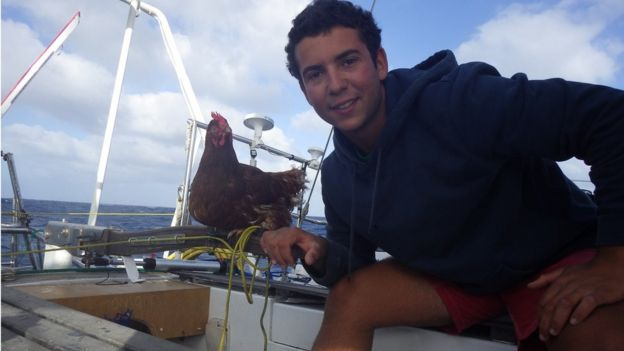 Sailor Guirec Soudee holding his hen Monique on the deck of a yacht