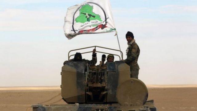 Myśliwce stoją w wieżyczce bojowego wózka piechoty pływającego pod banderą jednej z jednostek Popularnych Jednostek Mobilizacyjnych, idąc wraz z siłami Iraku przez prowincję Anbar, 25 listopada 2017 r.