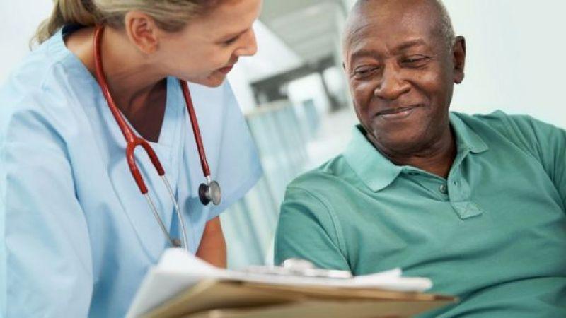 Enfermeira cuida de homem idoso, que sorri