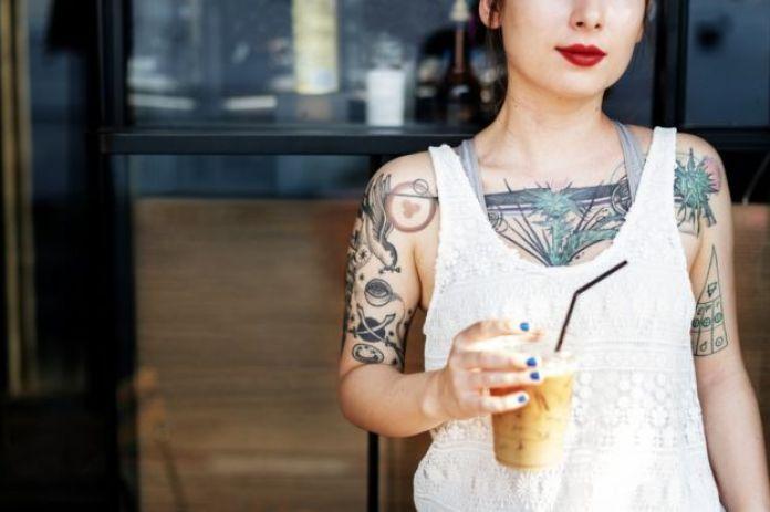 Chica con tatuajes en sus brazos y torso.