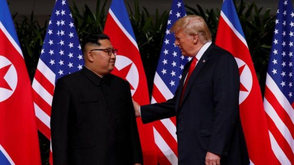 Donald Trump com a mão direita nas costas de Kim Jong-un
