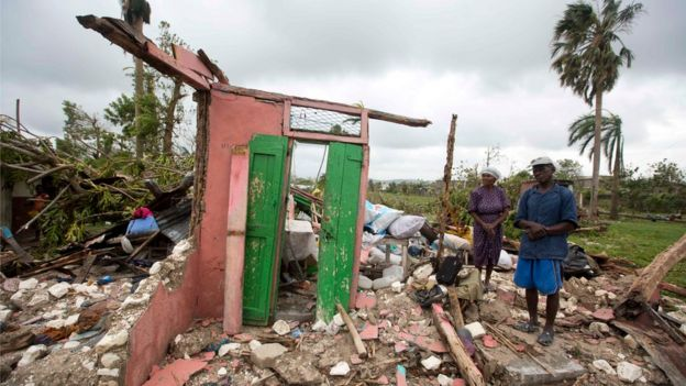 Residents next to their destroyed home