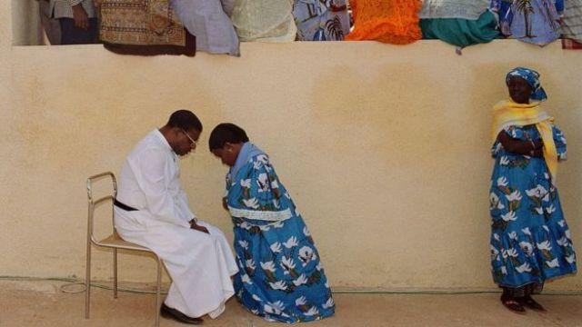 Une sénégalaise s'agenouille pour se confesser.
