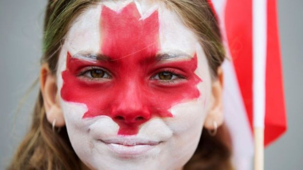 Clara Swain looks on with a painted face as she participates in the East York Toronto Canada Day parade, as the country marks its 150th anniversary with
