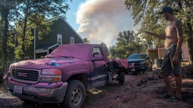 A resident looks at his truck covered in fire retardant as a smoke plume billows in the background near Oroville, California (08 July 2017)