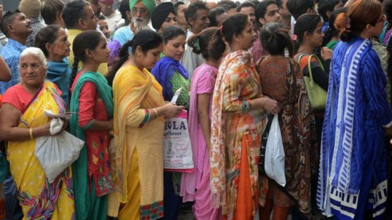Indian bank customers wait to deposit 500 and 1,000 rupee notes at a bank in Amritsar on November 10, 2016.