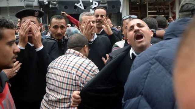 A group of Egyptian police personnel mourn outside the Saint Mark