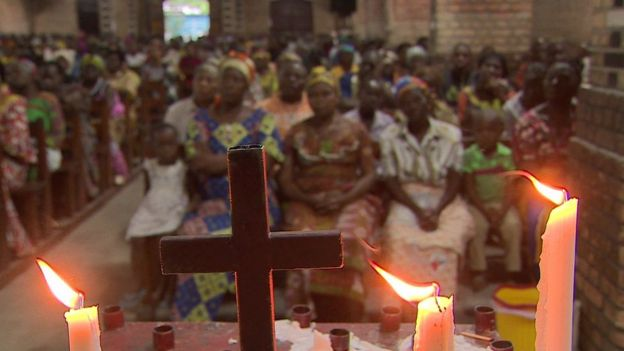 People sit in church with a cross and candles in the foreground
