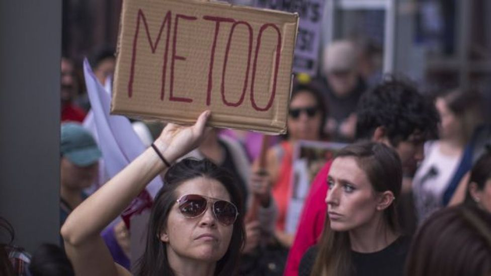 Una mujer sostiene una pancarta con el mensaje