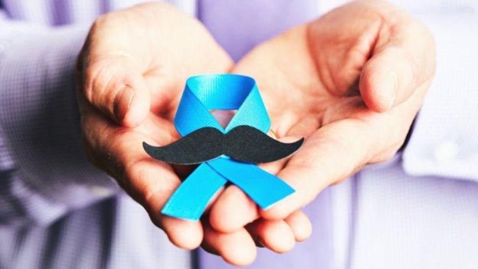 Hombre con el símbolo de concienciación del cáncer de próstata.