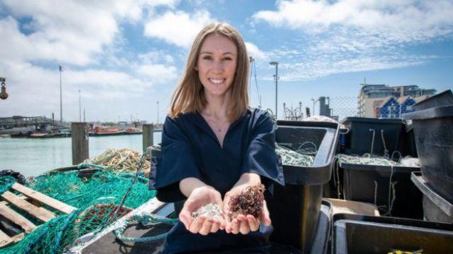 Lucy segurando o material que usou para criar sua alternativa a plástico