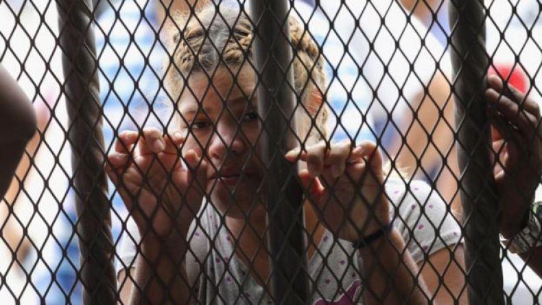 Una mujer detrás de las rejas en la frontera entre México y Guatemala.