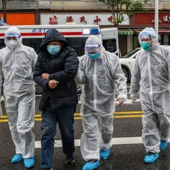 Medical staff members wearing protective clothing accompany a patient as they walk into a hospital in Wuhan