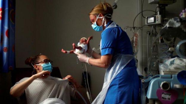 ممرضة تناول أما طفلها المولود للتو