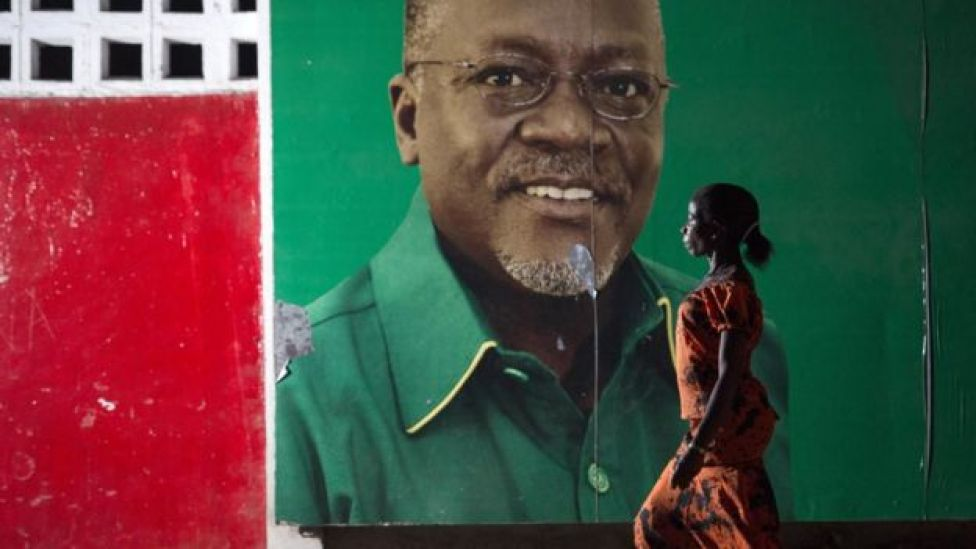A woman walks past an election poster for John Magufuli