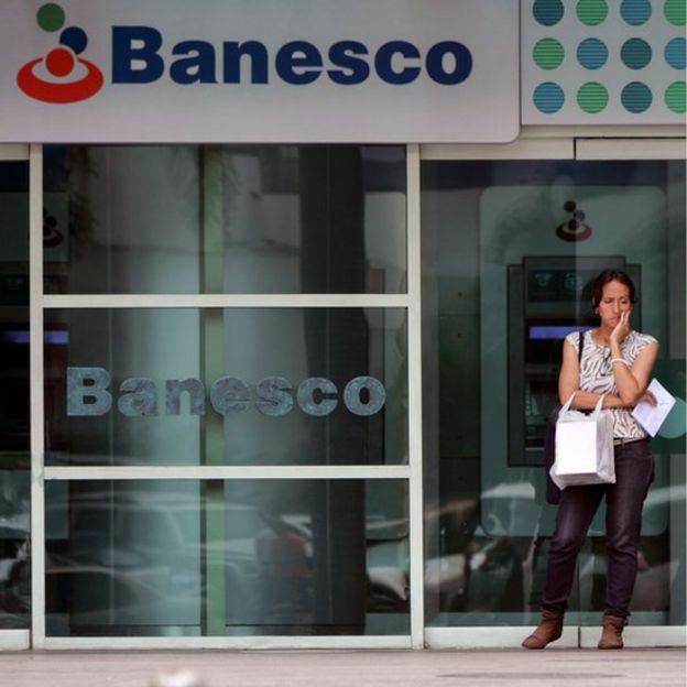 Una mujer ante un banco en Venezuela.