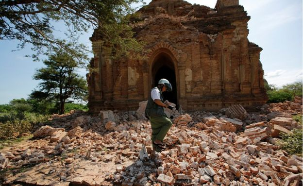 A photographer walks on the rubble of a collapsed pagoda after the earthquake. Taken 25 August 2016.