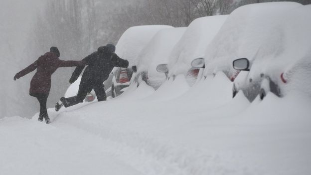 People cross a snow bank to get to the sidewalk on a residential street in Washington, DC on January 23, 2016