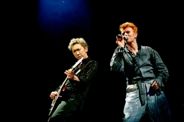 Photo of Hotei Tomayasu playing with David Bowie onstage at the Nippon Budokan in Tokyo in 1996