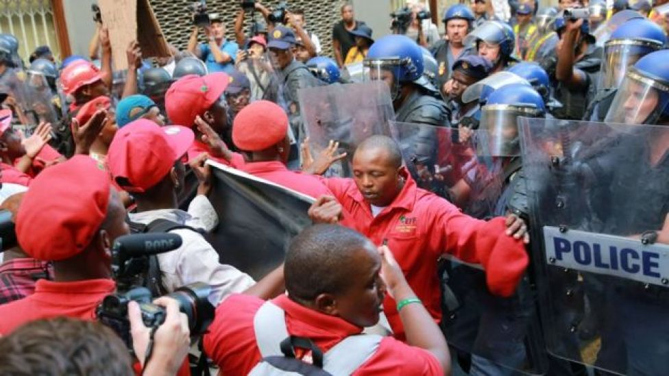 South African anti-riot police officers clash with members of South Africa's radical leftist Economic Freedom Fighters (EFF) party